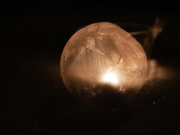 gefrorene Seifenblase im Schnee, Kristalle glitzern, dunkle Nacht, wunderschön, bizarr, Kerzenlicht beleuchtet die Kugel