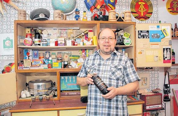 Heiko Orosz vor seinem Küchenbuffet voller Erinnerungen an die DDR. In einem Zimmer seiner Wohnung sammelt er Lebensmittel und Alltagsgegenstände. In der Hand hält er die Flasche Kirsch-Whisky mit der 1993 seine Sammelleidenschaft begann.