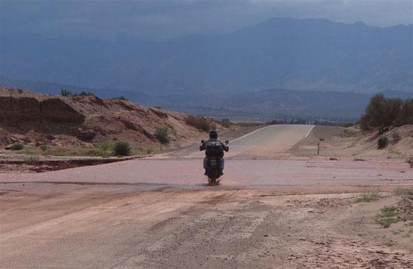 An dem Tag haben wir nur eine Gruppe an Motorradfahrern gesehen; der erste testet gerade die Furt. Zu dem Zeitpunkt wußten wir noch nicht, welche Auswirkung die dunkle Wand im Hintergrund haben wird. Wir selber sind nämlich nicht naß geworden ...