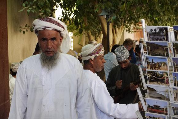 der Oman im Umbruch: der ältere Mann neben einem Postkartenständer, der auch die alten Zeiten zeigt, für die Touristen, mit denen neue Strukturen geschaffen und neue Lebensformen Einzug halten