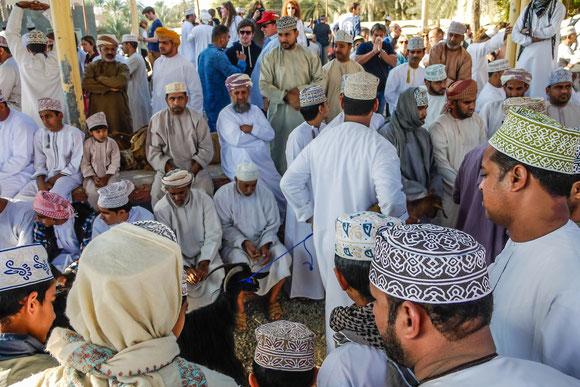 """hier werden gerade Tiere durchgeführt unter den kritischen Blicken der Männer im Vordergrund. Die Männer mit Turban auf der anderen Seite sind die """"Offiziellen"""", da die Omanis bei der Arbeit immer Turban tragen müssen und nicht ihr traditionelles Käppi."""