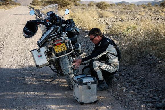 Im Schatten einer anderen Akazie stehend, kontrolliert Jan die Kabelbinder, mit denen wir diesmal verhindern wollen/werden, dass der Schmutzfänger abvibriert wie auf der ruta 40 in Argentinien.