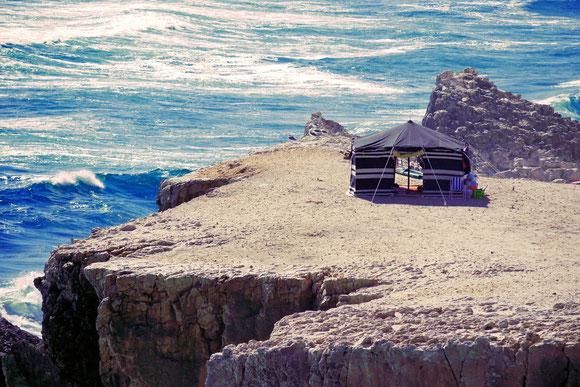 dieses Zelt gehört Einheimischen, 2 Geländewagen stehen in der Nähe, und die Männer sind gerade in der Bucht schwimmen.
