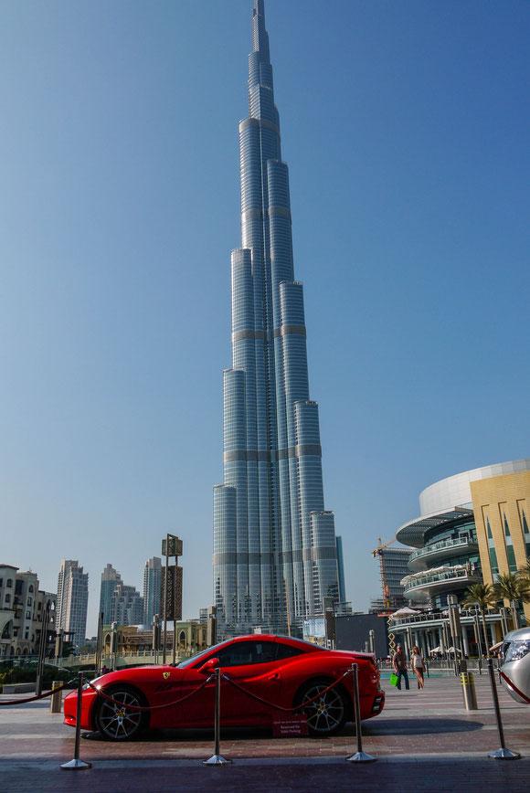 das höchste Haus der Welt passt natürlich nicht ganz auf ein Hochkant-Photo, wenn ein Ferrari im Vordergrund steht ;-). Ich als Frau habe mir in der Zwischenzeit lieber die 3 Motorräder aus Kuwait angesehen,die auch schon in Europa unterwegs gewesen waren