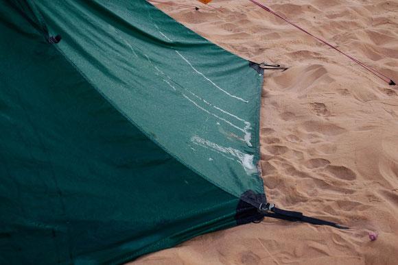 Wir konnten uns erinnern, dass man mit Loch in den Wüstenbogen graben und Plane darüber Kondenzwasser sammeln kann. Aber dass unser Zelt außen so nass sein kann, hätten wir in der Wüste nie vermutet. Das ist auch nicht zusammengestrichen o.ä.