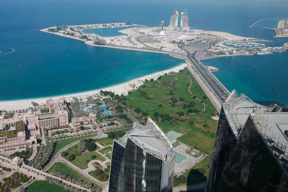 """und dann waren wir oben im 360 ° Cafe/Restaurant: links die Nebengebäude des Emirates Palace, vor uns eine """"Neubauinsel"""" mit den Anfängen eines Hotels mit Durchblick wie in Dubai,die linke Ecke der Insel ist bereits fertig mit kleinen Häuschen und Marina"""