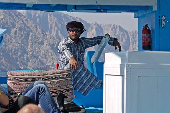 """unser Steuermann: er wußte, dass er sehr fotogen ist ;-)  Ganz selbstverständlich hat er gegen 15 h auf dem Boot seine """"Andacht"""" verrichtet: das Steuer dem 2. Mann übergeben, rituelle Fußwaschung, Gebetsteppisch ausgerollt und die vorgeschriebenen Gebete"""