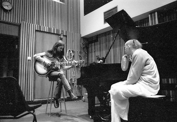 George recording a guitar part with devotees