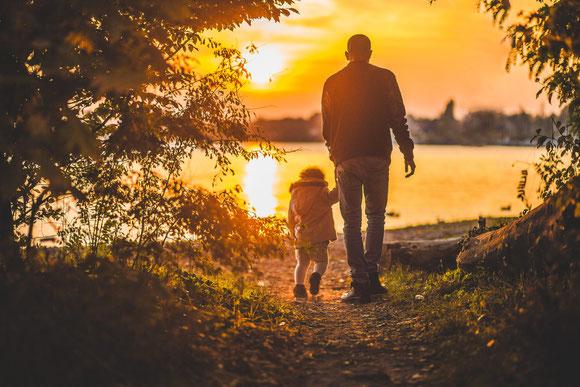 Vater mit Kind im Sonnenuntergang am Wasser