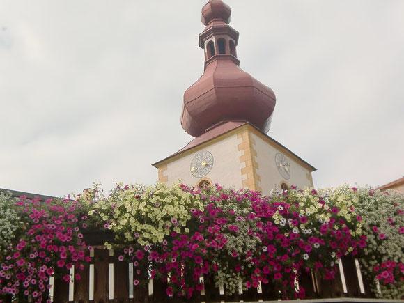 Auch hier  ist der ganze Ort mit vielen Blumen geschmückt.In der Nachmittagssonne sitzend gönnen wir uns eine kurze Rast