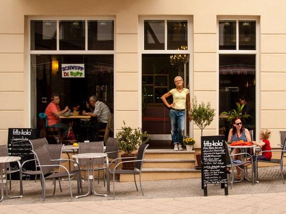 7 Tische und 20 bequeme Stühle, 2 große Schirme und mittlerweile jede Menge Grünzeug zaubern Sommerfeeling in unsere schöne Straße..