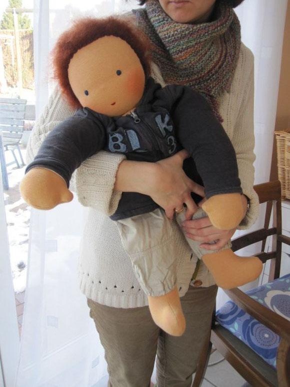 Joschi auf meinem Arm, in schon von meinen Kindern getragener Kleidung (so wird er in die Musikschule reisen)