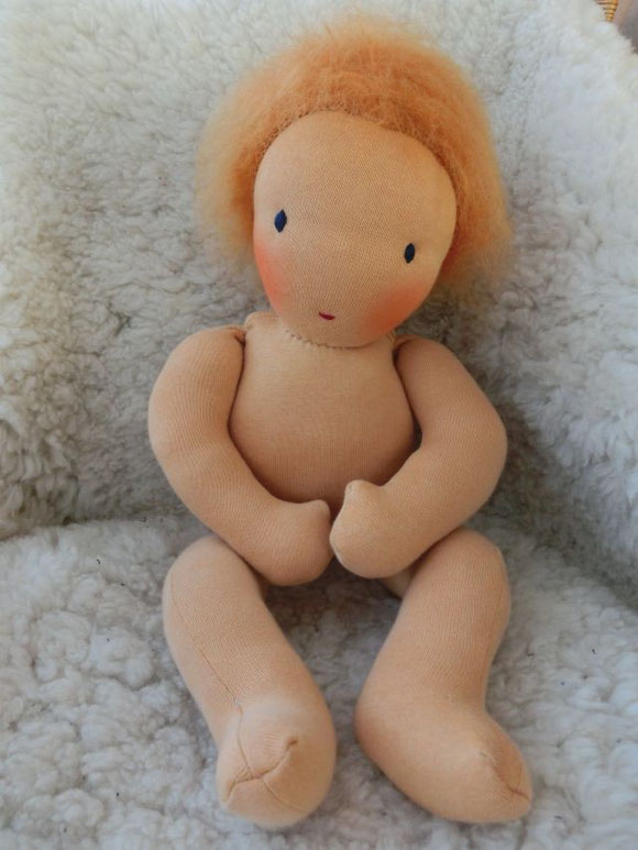 Dieses Babykind hat kupferfarbenes Haar und dunkelblaue Augen...