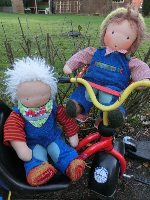 Die zwei Puppenbrüder im Partnerlook auf dem Dreirad...
