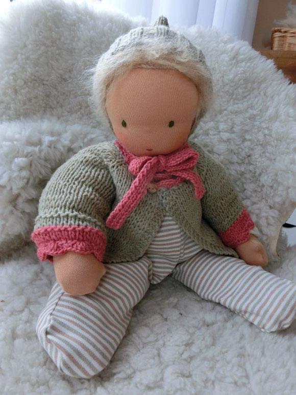 Baby 45cm groß, mit strohblondem Haar, einem Strampler aus dem schönen Bio-Ringeljersey auf farbig gewachsener Baumwolle, einer Nickiwindel (hier nicht zu sehen), einem Frottee-Shirt aus kbA-Baumwolle in creme, Strickjacke, Zipfelmütze (pflz.gefärbt)