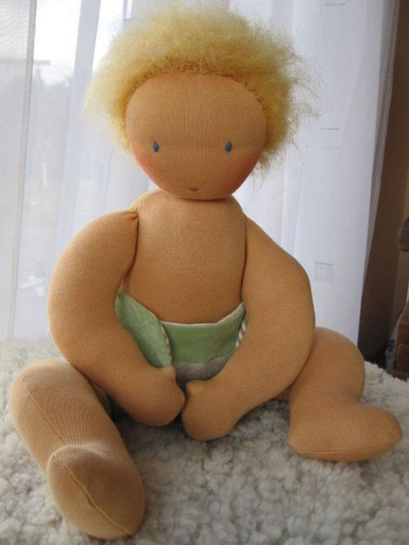 Das Baby kommt mit einer von mir genähten Nickiwindel mit Futter aus dem schönen Ringeljersey mit farbig gewachsener Baumwolle. Es kann frei sitzen.