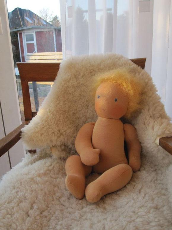 Evas Baby genießt die Abendsonne. Es hat goldblondes Mohair-Schurwoll-Flauschhhaar, leuchtend blaue Augen und ein kleines altrosa Mündchen. Es ist gefüllt mit Schafwolle und feinem Mineralgranulat.