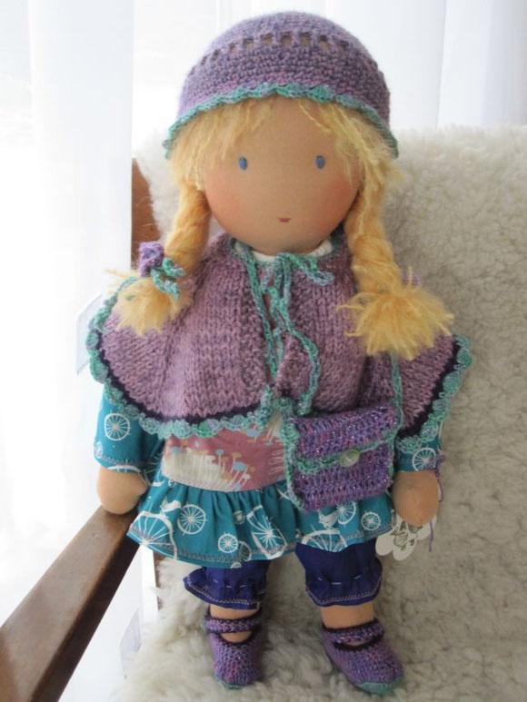 Sofias Puppe ist bekleidet mit einem Tunika-Kleid u. langer lila Batist-Unterhose (alle Stoffe GOTS-zertifiziert), einem aus doppeltem Faden gestrickten Umhang aus weichem Baby Alpaka Seidengarn, passend dazu Häkelmütze, Häkelballerinas u. Handtäschchen