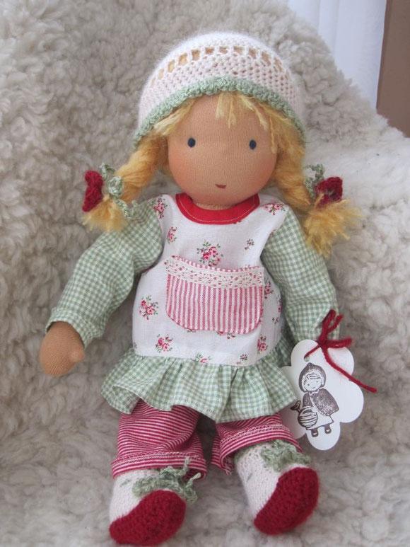 Margaretes Püppchen hat goldblondes Mohair-Schurwollhaar, dunkelblaue Augen und Kleidung ganz in rot, grün und weiß (Tunika-Kleid, Ringelleggings, Häkelstiefelchen und einfache Häkelmütze)