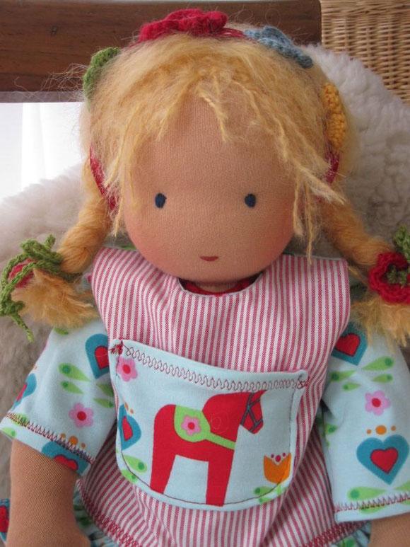 Agetha hat goldblondes Mohair-Schurwollhaar und dunkelblaue Augen