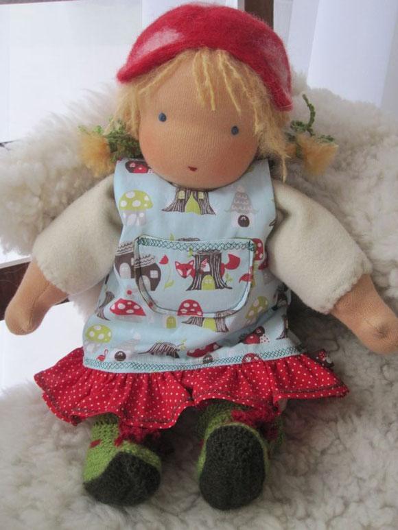 Das Puppenkind trägt ein Schürzenkleid aus Biostoff mit Fuchs und Waldszenen, passende Fliegenpilz-Filzkappe, eine Nickiwindel und Schühchen aus pflanzengefärbter Schurwolle (das helle grün) und Alpaka (das dunkle Grün)