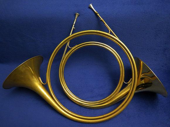Zwei Parforcehörner in Es-Dur, hergestellt vom Musikhaus Beck in Dettingen an der Erms, 2010er Jahre. Unten ein Horn mit dreieinhalb Windungen, oben ein Horn mit zweieinhalb Windungen. Seit 2016 bläst die JBG Schriesheim auf Beck Parforcehörnern.
