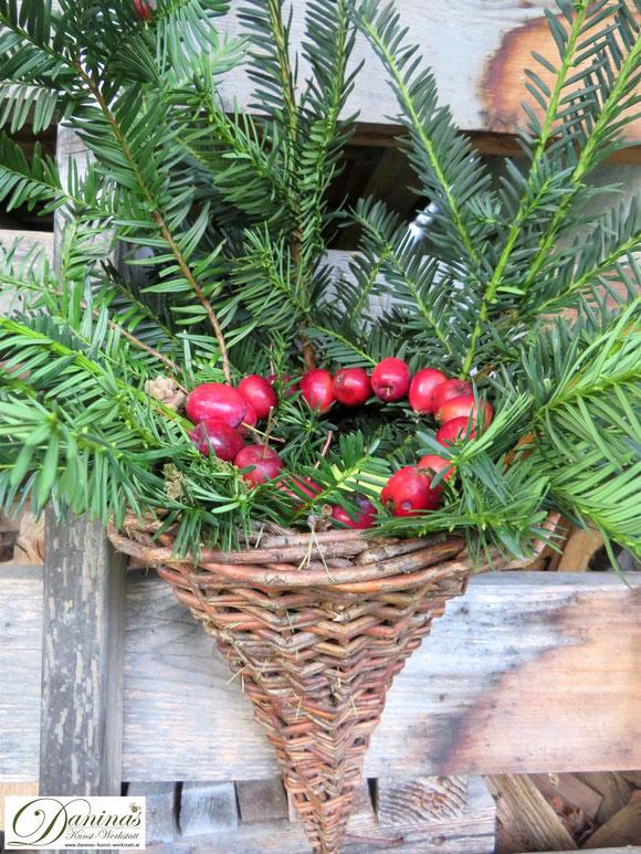 Herbstdeko für draussen: Eibenzweige und Zierapfel Kranz in Weidenkorb