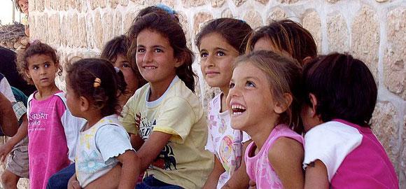 Fröhliche Kinder lachend vor einer Mauer