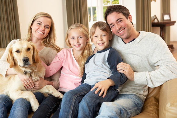 Family sitting a on couch smiling because wealth accumulation planning worked