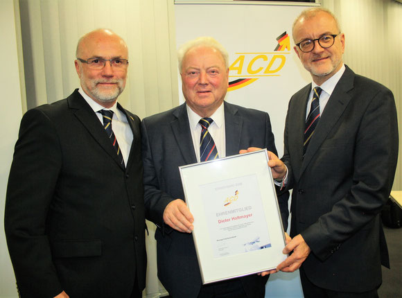 ACD board members Christoph Papke (left) and Winfried Hartmann (right) hand over the Certificate of Honour to Dieter Haltmayer  -  picture: hs