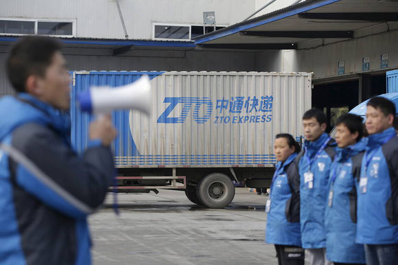Workers at a ZTO Express sorting centre in Beijing receive commands -  courtesy rtr
