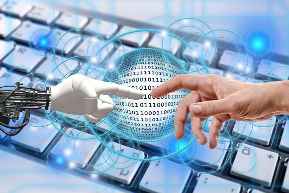 mano robot y mano humana sobre teclado