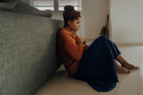 femme-avec-pill-orange-et-jupe-bleue-assise-par-terre-avec main-sur-la-poitrine