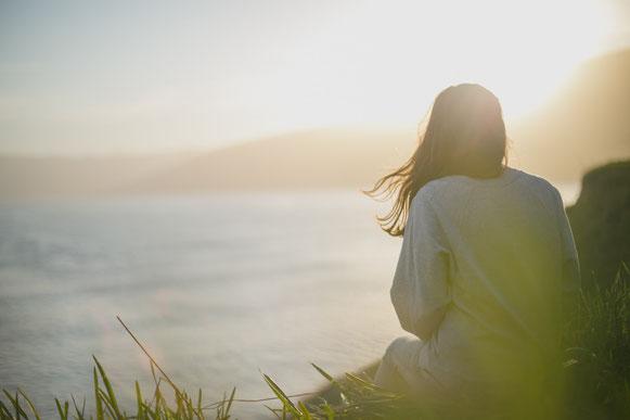 femme-de-dos-devant-la-mer-au-coucher-du-soleil