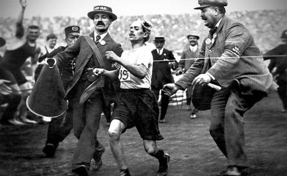 Dorando Pietri siendo ayudado por un oficial para cruzar la línea de meta del maratón de Londres 1908