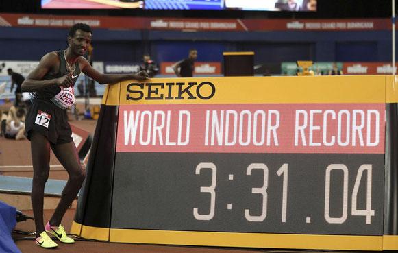 Samuel Tefera, de Etiopía, junto al indicador de tiempo, mientras celebra el récord mundial en pista cubierta de 1500 metros durante el Gran Premio Indoor de Muller en Birmingham, Inglaterra, el sábado 16 de febrero de 2019.  (David Davies / PA AP)