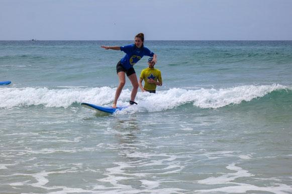 Surferin-reitet-Welle-im-Hintergrund-der-Surf-Lehrer