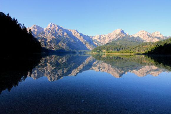 un lac fait miroir à tout ce qui se trouve sur la berge et au pont qui le traverse