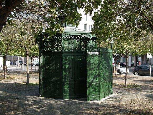 Des toilettes publiques vertes entourées d'arbres sur une place de ville