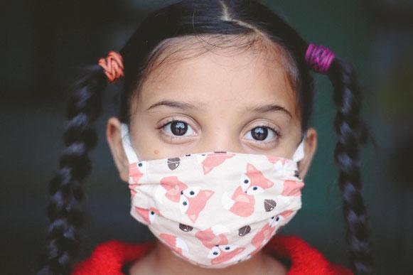 Petite fille bien brune avec des tresses couettes, et un masque fleuri