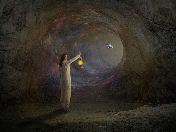 Un homme marche dans une grotte comme un tunnel, une lumière à la main.