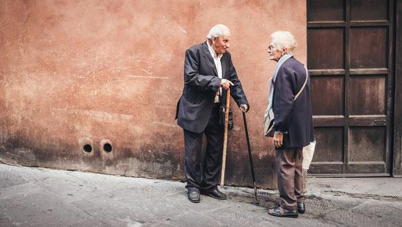 un homme âgé avec deux cannes discute avec une dame de son âge près d'une porte marron