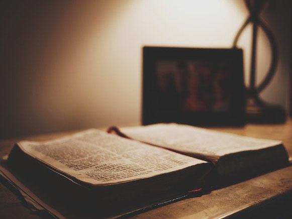 Une Bible ancienne dans les tons de sépia ouverte sur une table