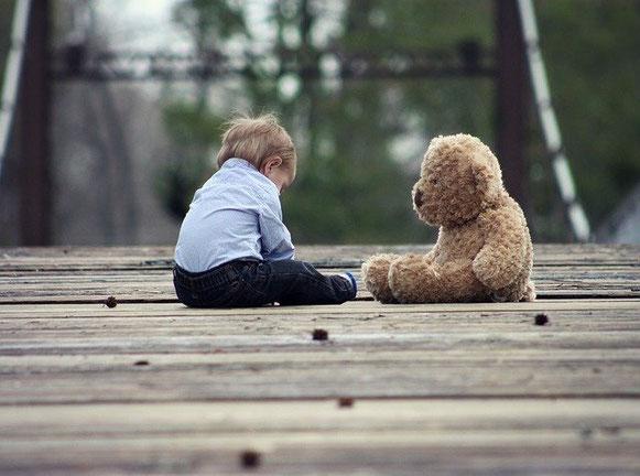 Un petit garçon assis par terre, face à son nounours en peluche