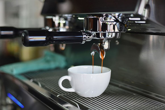 Une machine à café moderne qui verse du café dans une tasse blanche