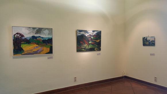 Drei Ölgemälde mit intensiven Farben und kräftiger Struktur in einer Ausstellung