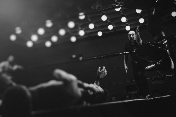 Ein schwarz weißes Bild von einem Boxring. Im Vordergrund liegt ein Boxer, der gerade K.O. geschlagen wurde. Ganz rechts Bild ist der Kampfrichter, der den Athleten anzählt.