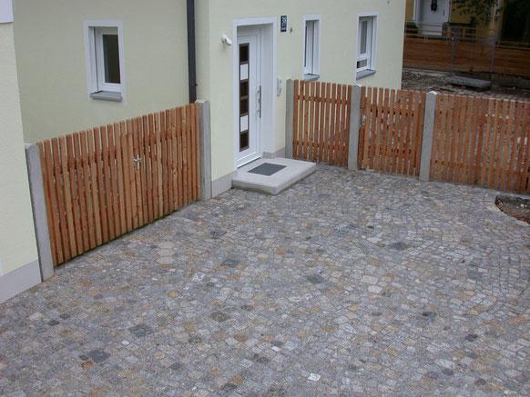 Bild: Einfahrt und Vorplatz aus Granit Mix. Verlegeart Eigenkreation. Staketenzaun und Tore aus Lärche. Pfosten Beton.