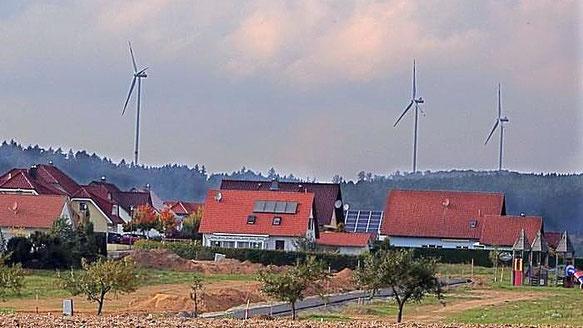 """Blick von der Wohnsiedlung """"Rhönblick"""" (Neubaugebiet am Lüderberg) in Bad Salzschlirf auf drei der fünf Windindustrieanlagen des """"Windparks Wartenberg""""."""