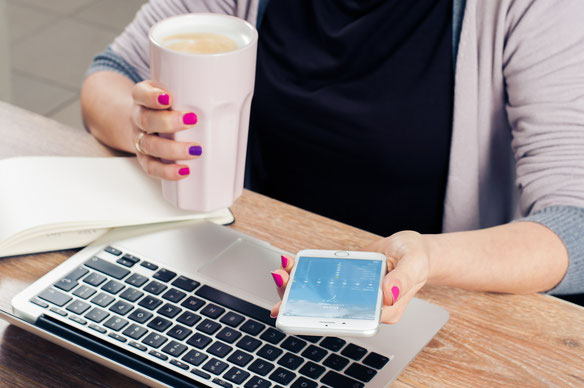 femme-qui-tient-une tasse-dans-sa-main-son-telephone-dans-l-autre-main-au-dessus-de-son-ordinateur-portable
